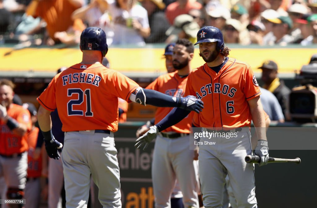 Derek Fisher #21 of the Houston Astros is congratulated by Jake Marisnick #6 after he hit a home run in the seventh inning against the Oakland Athletics at Oakland Alameda Coliseum on May 9, 2018 in Oakland, California.
