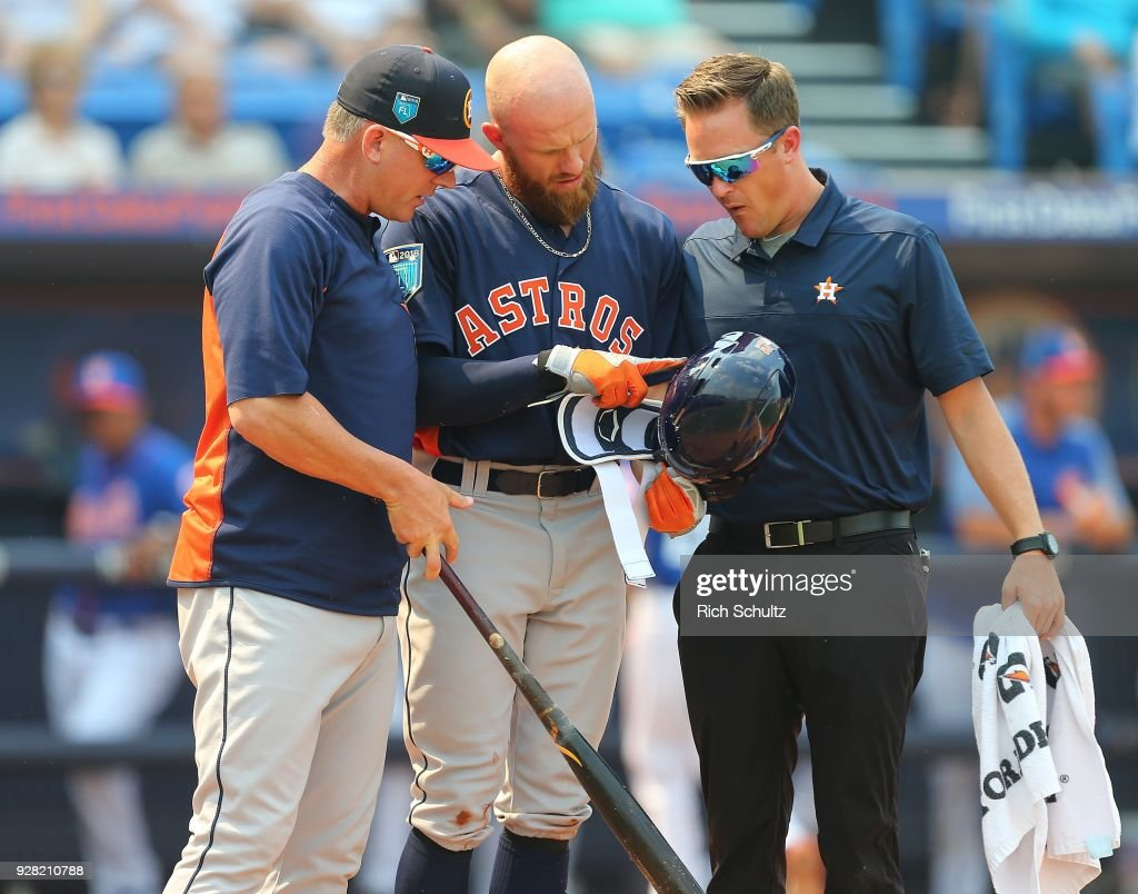 Derek Fisher #21 of the Houston Astros shows manager A.J. Hinch #14, left, and a team trainer the spot on his helmet that he got hit by a pitch from Jason Vargas #40 the New York Mets during the first inning of a spring training game at First Data Field on March 6, 2018 in Port St. Lucie, Florida. The Mets defeated the Astros 9-5.