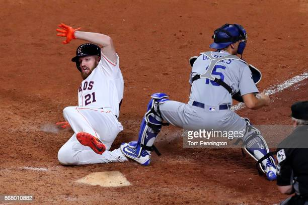 Derek Fisher of the Houston Astros slides in to home plate scoring the game winning run during the tenth inning against Austin Barnes of the Los...