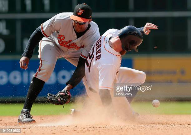 Derek Fisher of the Houston Astros steals second base as Jonathan Schoop of the Baltimore Orioles is unable to field the ball in the seventh inning...