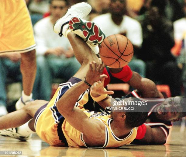 Derek Fisher of the Los Angeles Lakers and Hakeem Olajuwon of the Houston Rockets tangle on the floor as they go for a loose ball during their first...