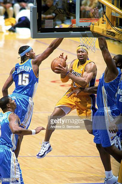 Derek Fisher of the Los Angeles Lakers goes to the basket against Carmelo Anthony of the Denver Nuggets during the NBA game at Staples Center on...