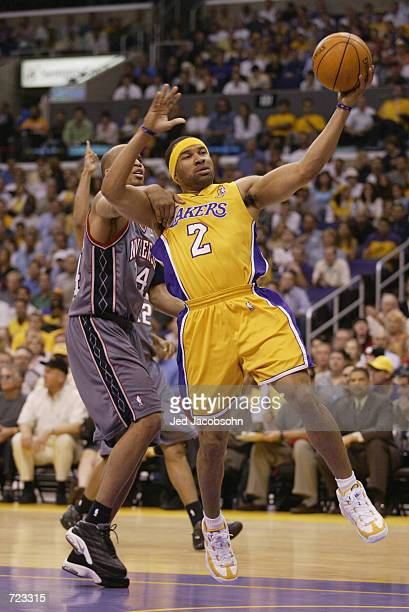 Derek Fisher of the Los Angeles Lakers goes to the basket past Richard Jefferson of the New Jersey Nets during Game one of the 2002 NBA Finals at...