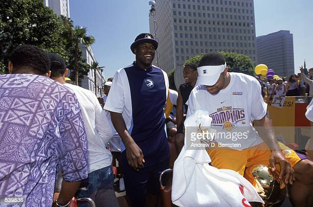 Derek Fisher of the Los Angeles Lakers polishes the trophy as Shaquille O'Neal moves to greet fans on the parade route honoring their third...