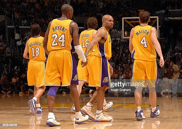 Derek Fisher of the Los Angeles Lakers slaps hands with teammate Kobe Bryant as the rest of the Lakers walk back to their bench while taking on the...