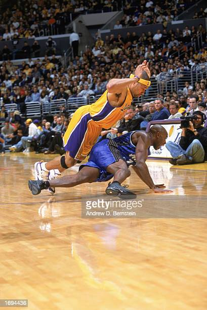 Derek Fisher of the Los Angeles Lakers tries not to foul Jacque Vaughn of the Orlando Magic as he falls at Staples Center on December 15 2002 in Los...