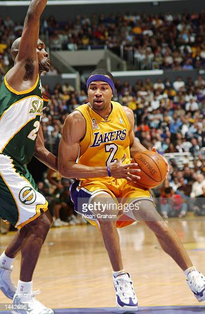 Derek Fisher of the Los Angeles Lakers tries to get to the basket past Gary Payton of the Seattle SuperSonics during the first half of action at...