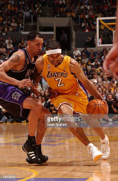 Derek Fisher of the Los Angeles Lakers tries to get to the basket past Doug Christie of the Sacramento Kings during the first half at Staples Center...