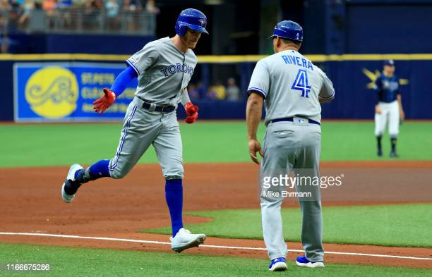 Derek Fisher of the Toronto Blue Jays is congratulated after hitting a two run home run in the sixth inning during a game against the Tampa Bay Rays...