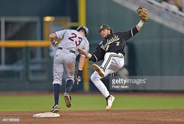 Derek Fisher of the Virginia Cavaliers slides into second with a stolen base as second baseman Dansby Swanson of the Vanderbilt Commodores is knocked...