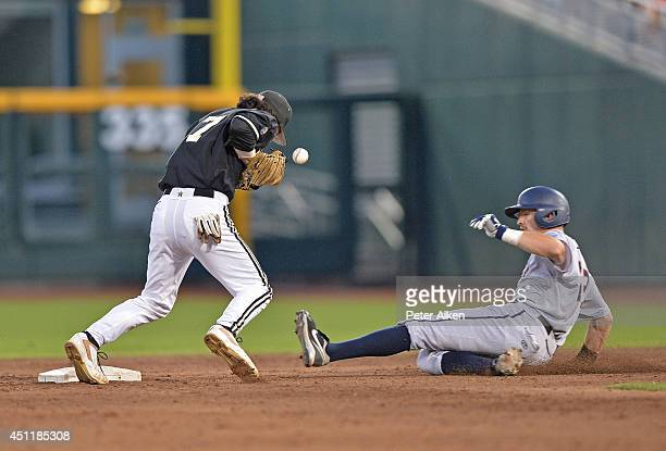 Derek Fisher of the Virginia Cavaliers slides into second with a stolen base as second basemen Dansby Swanson of the Vanderbilt Commodores bobbles...