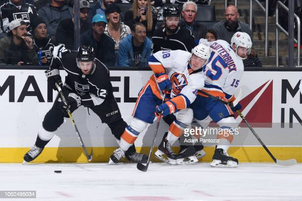 Derek Forbort and Nate Thompson of the Los Angeles Kings and Anthony Beauvillier and Cal Clutterbuck of the New York Islanders battle for the puck...