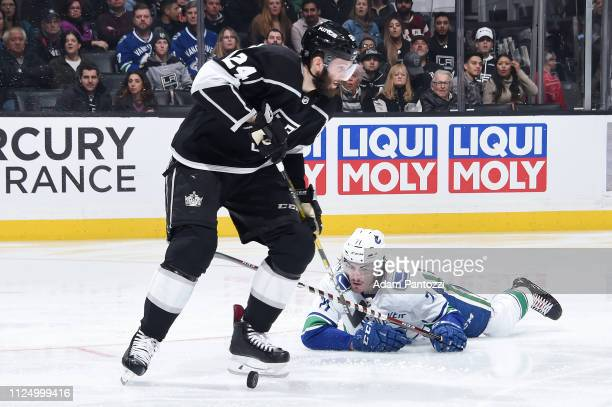 Derek Forbort of the Los Angeles Kings skates with the puck as Zack MacEwen of the Vancouver Canucks falls to the ice during the second period of the...