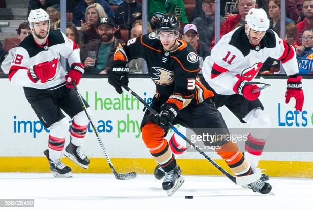 Derek Grant of the Anaheim Ducks skates with the puck with pressure from Brian Boyle of the New Jersey Devils during the first period of the game at...