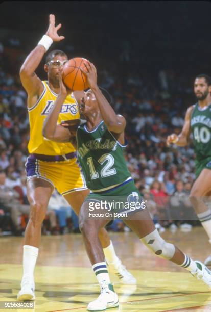 Derek Harper of the Dallas Maverick drives to the basket on Kareem AbdulJabbar of the Los Angeles Lakers during an NBA basketball game circa 1989 at...