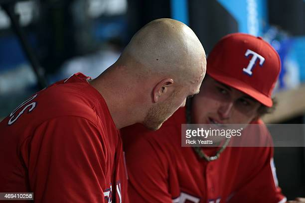 Derek Holland of the Texas Rangers talks with Jon Edwards after being relieved in the sixth inning against the Houston Astros at Globe Life Park in...