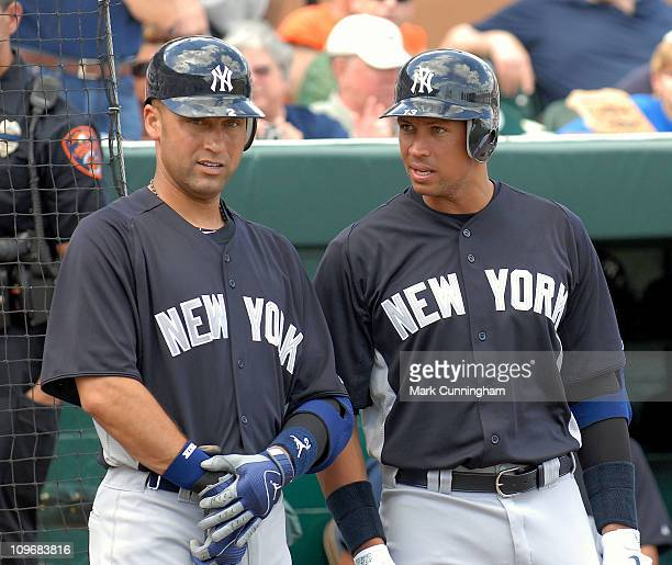 Derek Jeter and Alex Rodriguez of the New York Yankees look on against the Detroit Tigers during the spring training game at Joker Marchant Stadium...