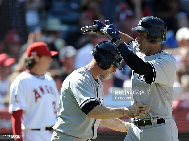 Derek Jeter and Brett Gardner of the New York Yankees celebrate their two runs for a 65 lead in front of pitcher Scott Downs of the Los Angeles...