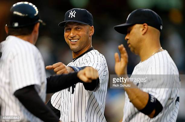 Derek Jeter and Carlos Beltran of the New York Yankees are congratulated by teammates after defeating the Kansas City Royals 62 in a MLB baseball...