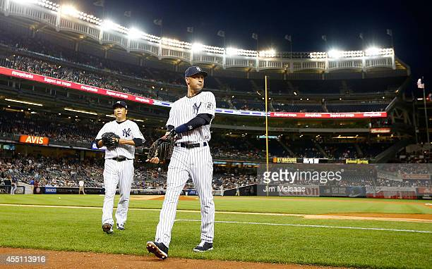 Derek Jeter and Hiroki Kuroda of the New York Yankees walk to the dugout after an inning against the Tampa Bay Rays at Yankee Stadium on September 9...