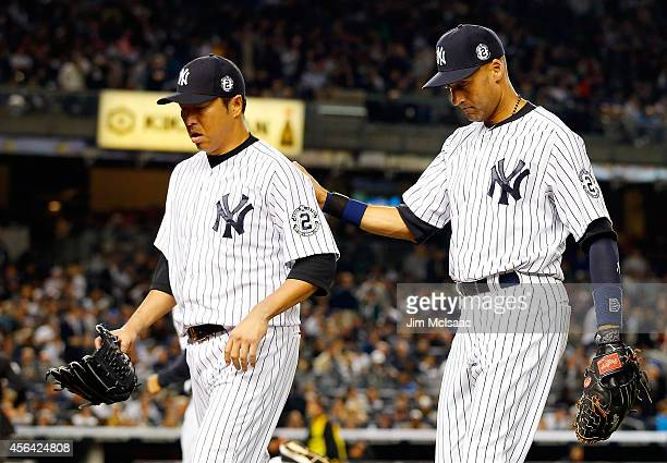Derek Jeter and Hiroki Kuroda of the New York Yankees walk to the dugout after the seventh inning against the Baltimore Orioles at Yankee Stadium on...
