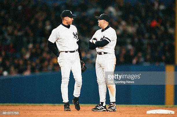 Derek Jeter and Luis Sojo of the New York Yankees talk during Game One of the American League Championship Series against the Seattle Mariners on...
