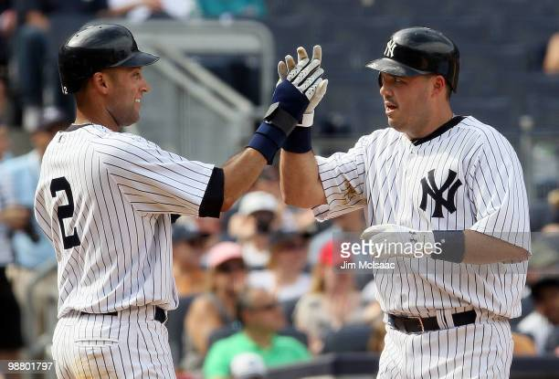 Derek Jeter and Nick Johnson of the New York Yankees celebrate after scoring in the seventh inning against the Chicago White Sox after a double from...