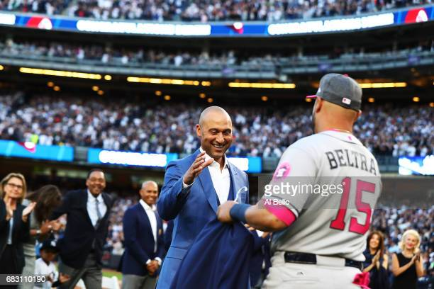 Derek Jeter is met by former teamate Carlos Beltran of the Houston Astros during the retirement ceremony of his number 2 jersey at Yankee Stadium on...