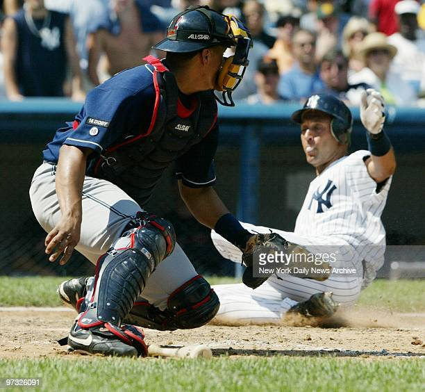 Derek Jeter keeps his bubble gum under control as he slides home with the New York Yankees' seventh run and the sixth in the sixrun sixth inning...