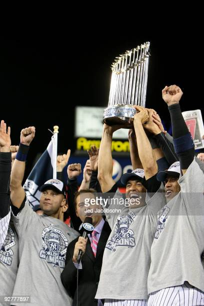 Derek Jeter Mariano Rivera and Robinson Cano of the New York Yankees celebrate with the trophy after their 73 win against the Philadelphia Phillies...