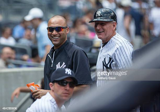 Derek Jeter of the New York Yankees and first base coach Mick Kelleher smile in the dugout during the game against the Detroit Tigers at Yankee...