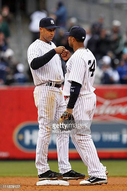Derek Jeter of the New York Yankees and teammate Robinson Cano celebrate their 63 win over the Detroit Tigers on Opening Day at Yankee Stadium on...