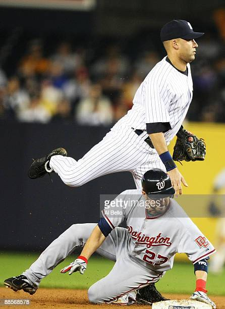 Derek Jeter of the New York Yankees avoids the slide of Wil Nieves of the Washington Nationals during their game on June 18 2009 at Yankee Stadium in...