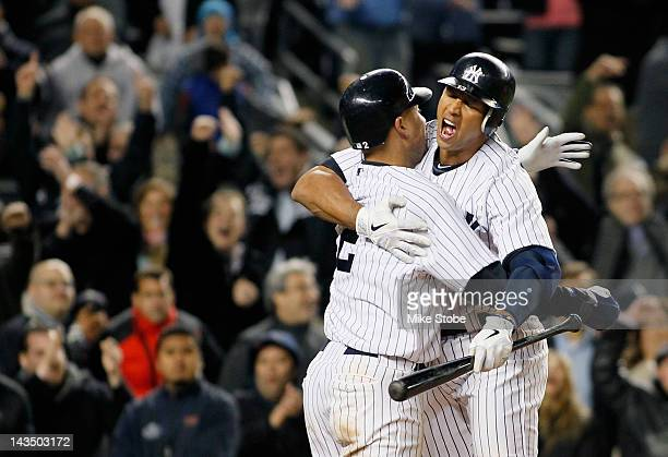 Derek Jeter of the New York Yankees celebrates after scoring the game winning run on a past ball with teammate Alex Rodriguez in the bottom of the...