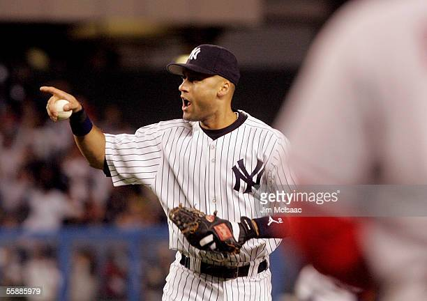 Derek Jeter of the New York Yankees celebrates as he points to Jorge Posada after tagging out Vladimir Guerrero of the Los Angeles Angels of Anaheim...