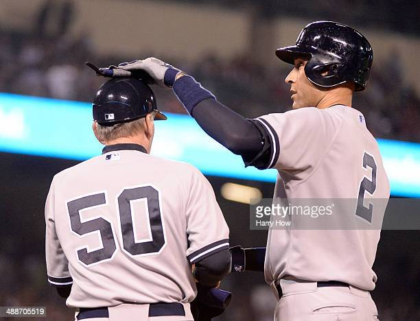 Derek Jeter of the New York Yankees celebrates his single with first base coach Mick Kelleher during the fourth inning against the Los Angeles Angels...