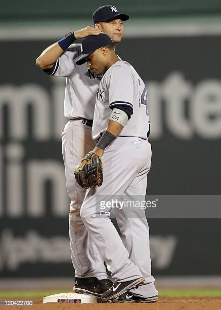 Derek Jeter of the New York Yankees celebrates the win with teammate Robinson Cano after the game against the Boston Red Sox on August 5 2011 at...