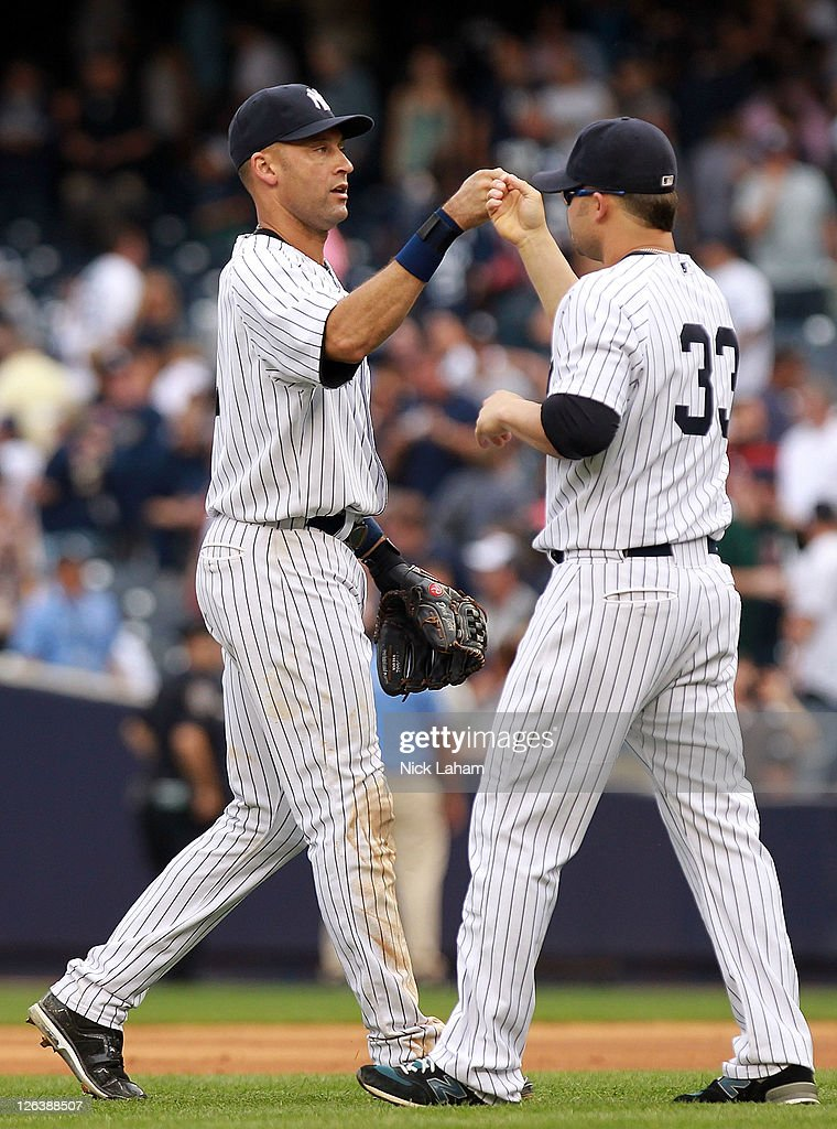 Derek Jeter #2 of the New York Yankees celebrates the win with teammate Nick Swisher #33 against the Boston Red Sox on September 25, 2011 at Yankee Stadium in the Bronx borough of New York City.