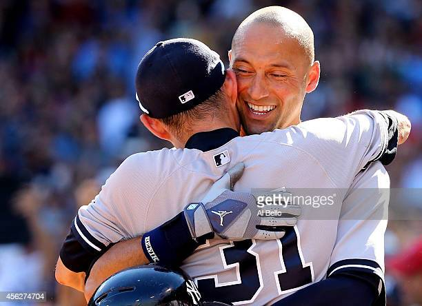 Derek Jeter of the New York Yankees celebrates with Ichiro Suzuki after hitting a single for his last career at bat in the third inning against the...