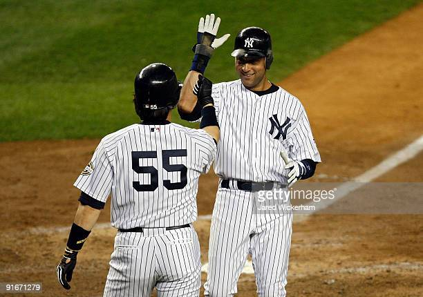 Derek Jeter of the New York Yankees celebrates with teammate Hideki Matsui after scoring a run in sixth inning against the Minnesota Twins in Game...