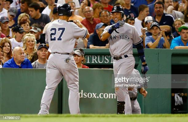 Derek Jeter of the New York Yankees congratulates teammate Raul Ibanez after Ibanez scored against the Boston Red Sox during the game on July 6 2012...