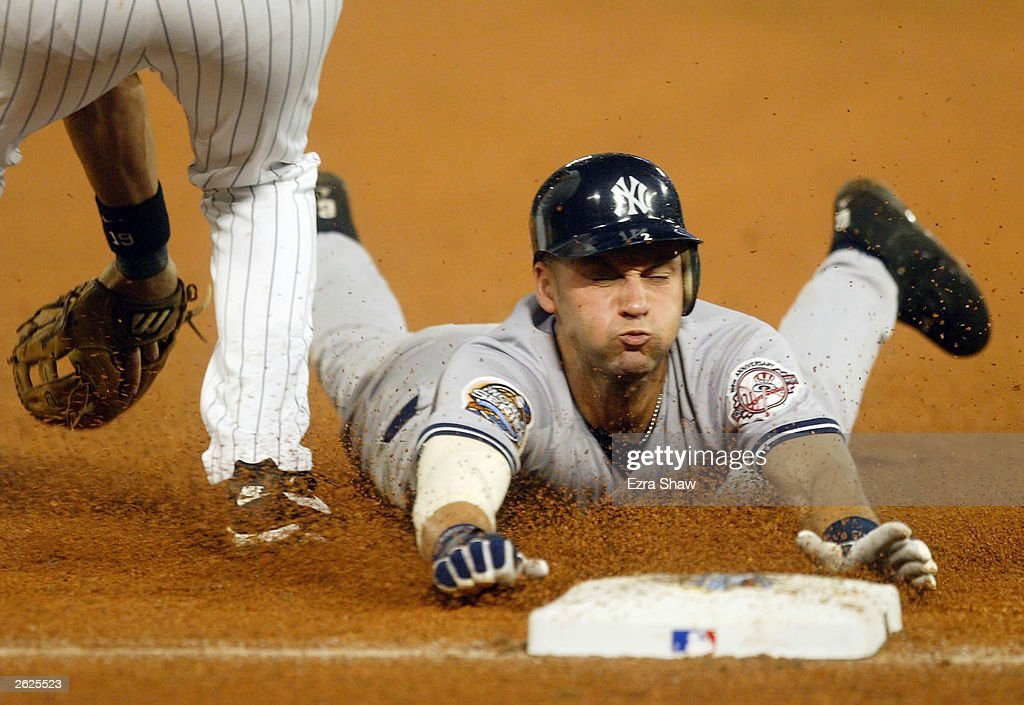 Derek Jeter #2 of the New York Yankees dives safely into third base after advancing on a Bernie Williams #51 pop fly in the eighth inning against the Florida Marlins during Game 3 of the Major League Baseball World Series October 21, 2003 at Pro Player Stadium in Miami, Florida.
