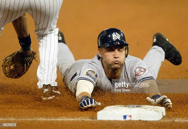 Derek Jeter of the New York Yankees dives safely into third base after advancing on a Bernie Williams pop fly in the eighth inning against the...
