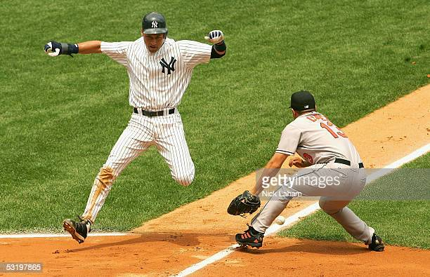 Derek Jeter of the New York Yankees evades the tag of Rodrigo Lopez of the Baltimore Orioles on the way to scoring a run in the fourth on July 5,...