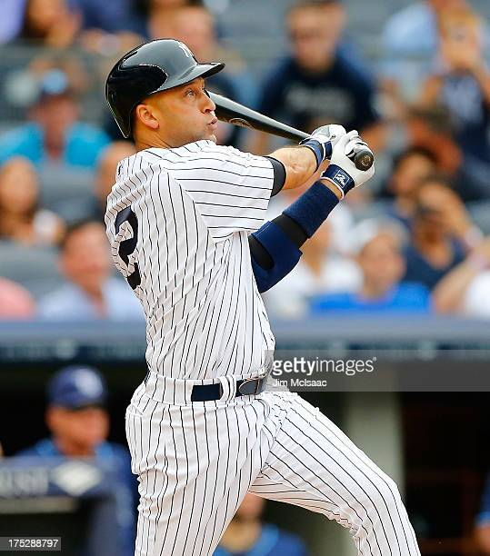 Derek Jeter of the New York Yankees follows through on a first inning home run against the Tampa Bay Rays at Yankee Stadium on July 28, 2013 in the...