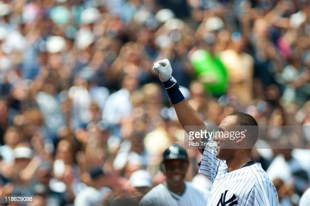 Derek Jeter of the New York Yankees gestures to the crowd after hitting a home run and collecting his 3000 hit of his career in the third inning...