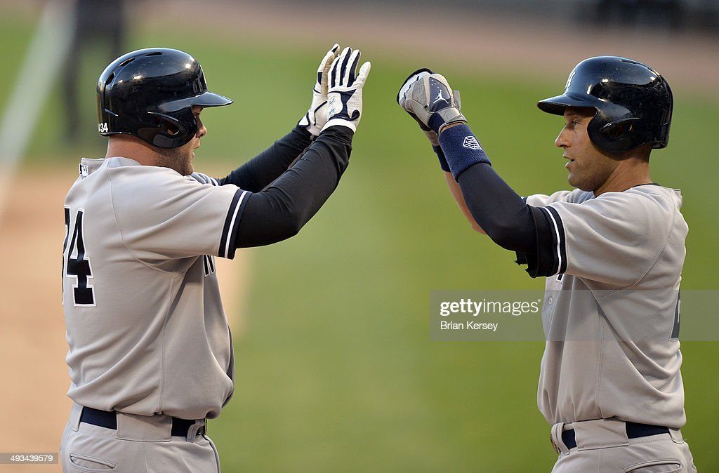 Derek Jeter #2 of the New York Yankees (R) high-fives teammate Brian McCann #34 after McCann hit a three-run home run scoring Jeter and Mark Teixeira during the first inning against the Chicago White Sox at U.S. Cellular Field on May 23, 2014 in Chicago, Illinois.