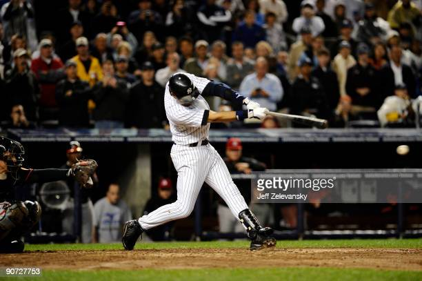 Derek Jeter of the New York Yankees hits a single to right field in the third inning during a game against the Baltimore Orioles at Yankee Stadium on...