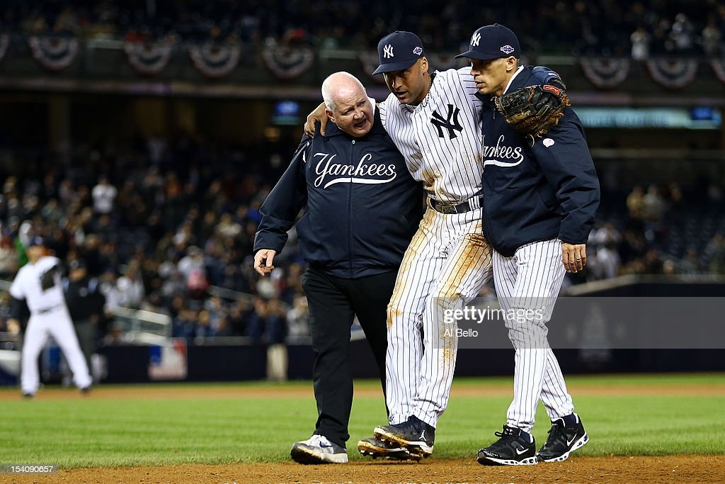 Derek Jeter #2 of the New York Yankees is carried off of the field by trainer Steve Donohue (L) and manager Joe Girardi after Jeter injured his leg in the top of the 12th inning against the Detroit Tigers during Game One of the American League Championship Series at Yankee Stadium on October 13, 2012 in the Bronx borough of New York City, New York.
