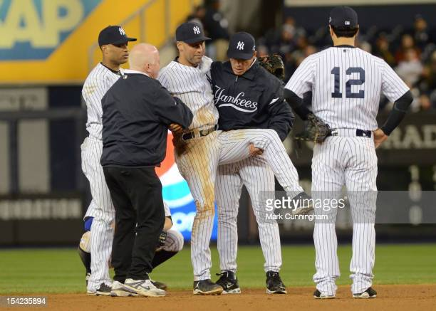 Derek Jeter of the New York Yankees is carried off the field by trainer Steve Donohue and manager Joe Girardi after Jeter fractured his left ankle in...